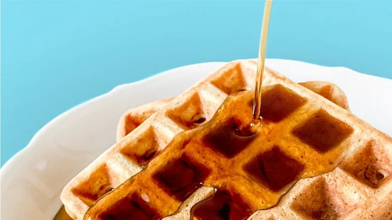A white plate filled with two square waffles, topped with maple syrup.