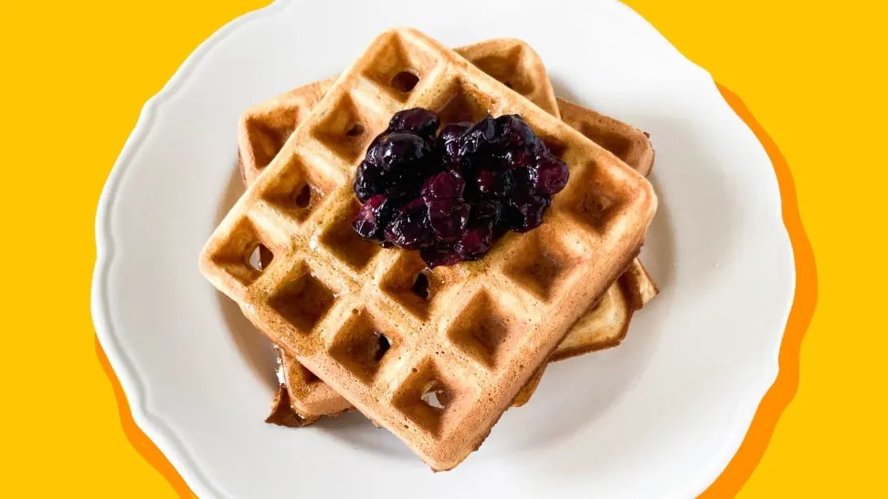Two waffles with blueberry compote on top sitting on a white plate on a white surface.