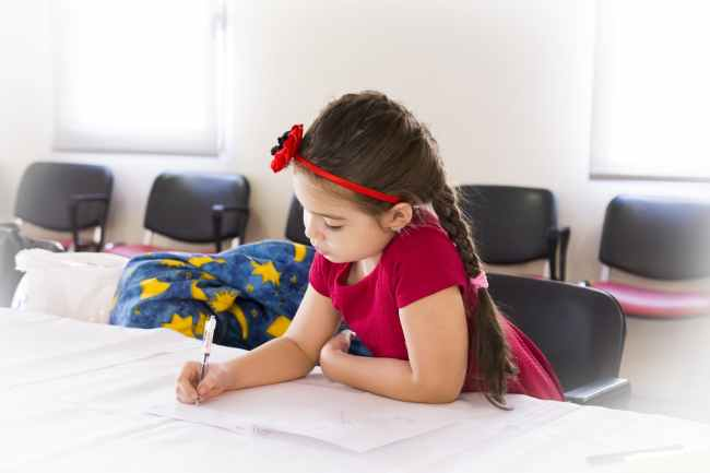 A girl is sitting at a table in an empty room with pen and paper