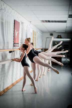 A group of girls are holding a ballet bar and moving a leg up and down. The legs are all in different ranges of motions.