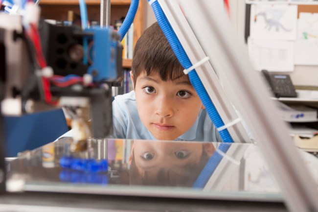 A young boy watches as a 3D printer prints an object.