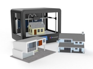 3d printer with a model house being printed and two already done in front of the printer