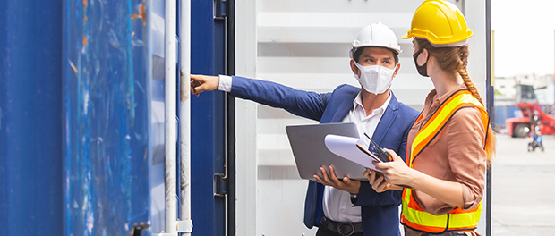 Teamwork foreman man and woman wearing protection face mask and safety helmet using laptop and holding clipboard checking containers in cargo ship for import export, Industrial container cargo concept.