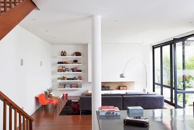 La columna central entrefunciones de piso y la sala y el comedor esmesa de granito negro, un gesto típico de ladonde los propietarios arquitectura de la décadacolocaron unos libros de 1950.