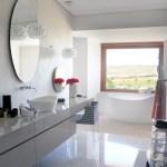 Izquierda. El mármol de Carrara, el brillo de las griferías cromadas, los espejos y el blanco de los muros y la tina imponen una atmósfera austera que contrasta con el color del paisaje de la meseta castellana.