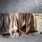 Pieles Apache y Novapelle con terminado semianilina para máxima suavidad, en colores contemporáneos y clásicos, de P. Vergara. Pedestal Trípode Imperio en tonos gris y oro, de Becara.