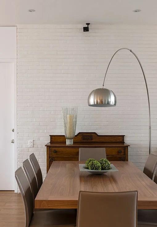 El comedor es una mezcla de estilos. Sobresale el contraste entre el clásico bifé, la moderna lámpara de piso y la mesa contemporánea de flor morado acompañada de sillas de líneas rectas y sencillas de BoConcept. El muro de ladrillo da textura al espacio y aporta profundidad y luminosidad a la zona social.