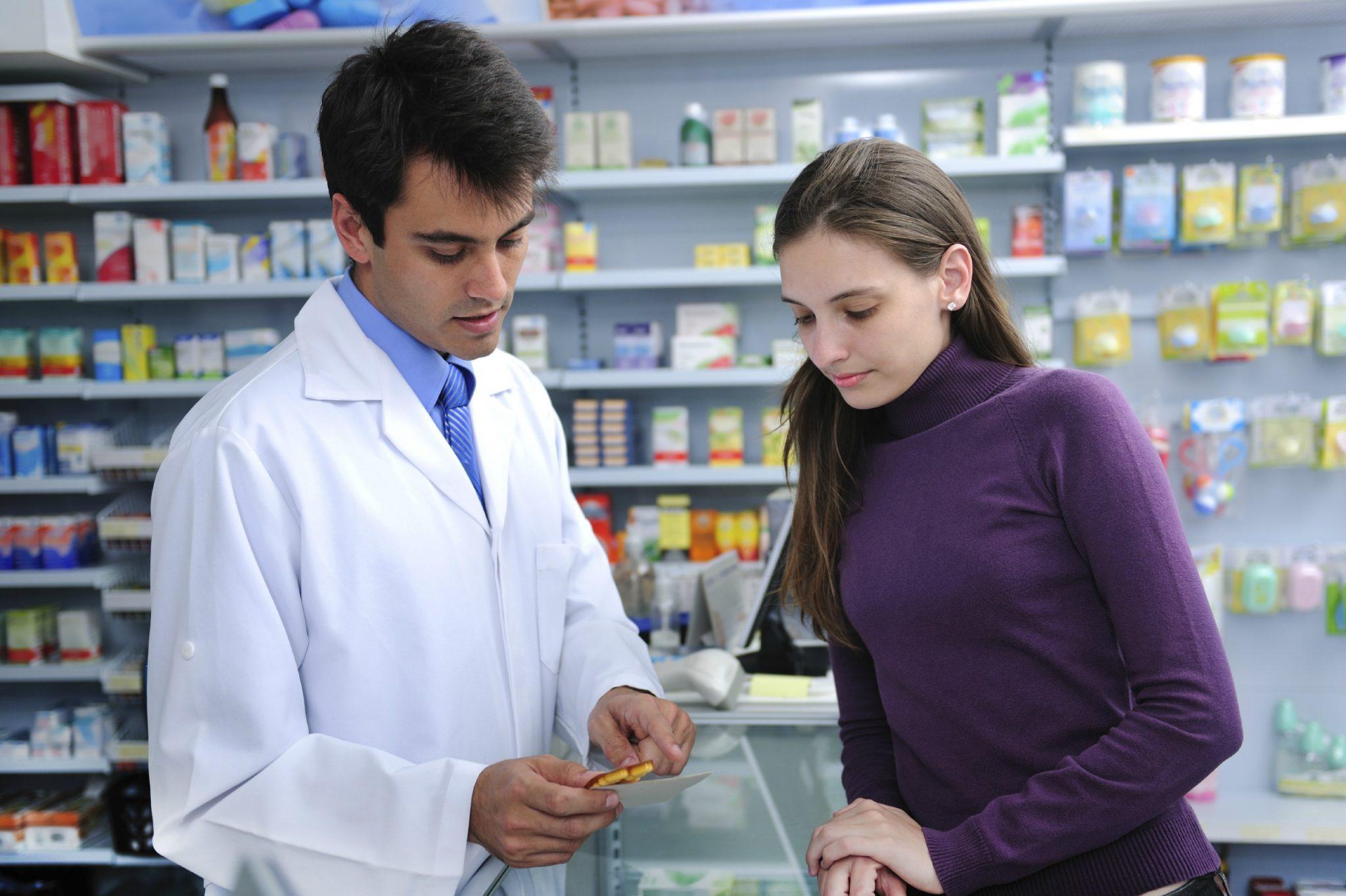 Farmacêutico mostrando um medicamento para compradora na bancada da farmácia