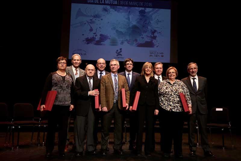 El president, l'alcalde i els responsables de la mútua, amb els socis i treballadors homenatjats en l'acte. Foto: Rubén Moreno