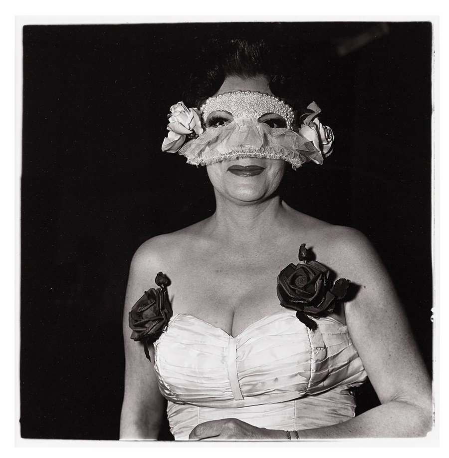 Diane Arbus. Lady at a masked ball with two roses on her dress 1967. © The state of Diane Arbus