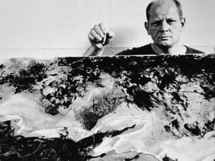 American abstract expressionist painter Jackson Pollock (1912 - 1956) holds a cigarette above and behind one of his paintings in his studio at 'The Springs,' East Hampton, New York, August 23, 1953. (Photo by Tony Vaccaro/Getty Images)