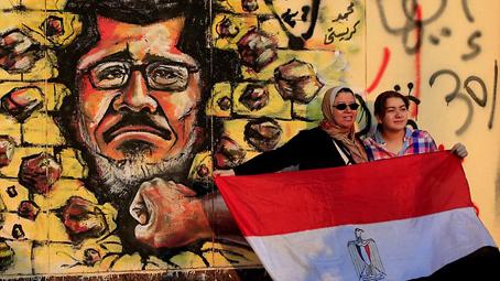 Mujeres con la bandera egipcia frente a un mural de Morsi. Foto © AP.