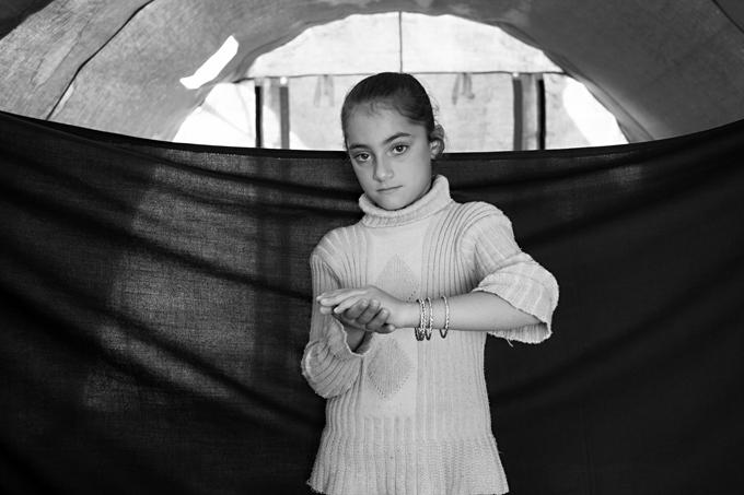 May, 8 años, en el campo de refugiados de Domiz, Kurdistán, Iraq (16 de noviembre de 2012). May y su familia huyeron de Damasco, Siria, por la noche. May lloró durante todo el recorrido, sufriendo frío, mientras su madre llevaba a su hermano de 2 años en brazos. Desde su llegada a Domiz, May tiene pesadillas en las que su padre es asesinado violentamente. Lo más importante que pudo llevarse son las pulseras que luce en la fotografía. «Las pulseras no son mis cosas favoritas. Mi objeto favorito es mi muñeca Nancy, pero con las prisas me la olvidé sobre mi cama. Foto © Brian Sokol.
