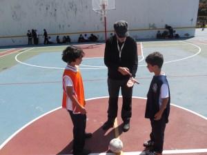 El profesor Manuel Urbano sorteando campo entre dos equipos contendientes.