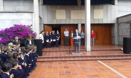 El profesor Valentín Velasco dirigiéndose a los presentes con el Equipo Directivo al fondo acompañando a Doña  Zulan Popa Danel Ministra Cpnsejera de la Embajada de Cuba en Colombia (Pantalón naranja)