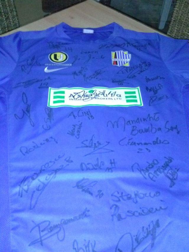 Camisa de seu novo clube, o Mosta FC. Abaixo da logo do patrocinador, a esquerda está a assinatura de Mandinho.