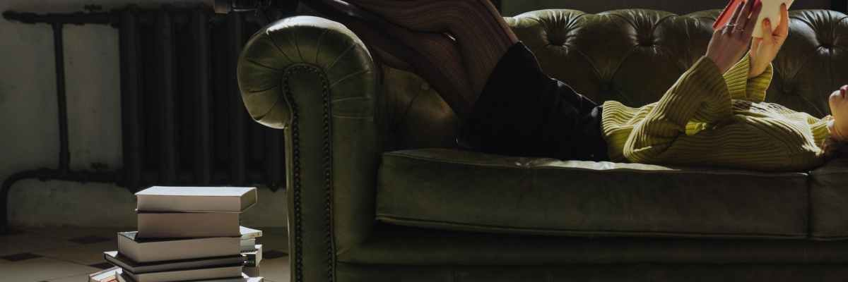 man in black jacket lying on white leather sofa chair