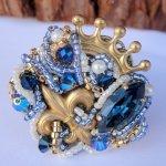 Broche qui représente une couronne et un lys dorés, parsemés de perles bleues, à l'effigie de la Royauté