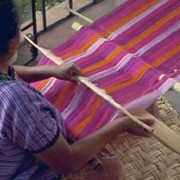 A member of the Cojolya Association weaves colorful textiles on a backstrap-loom