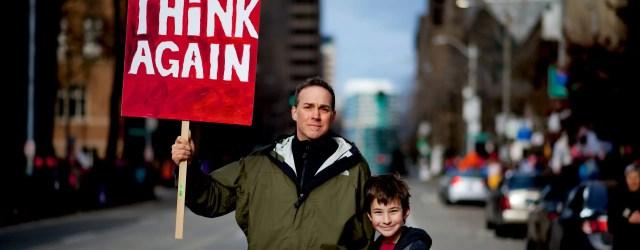 """papa et fils avec panneau """"make america think again"""""""