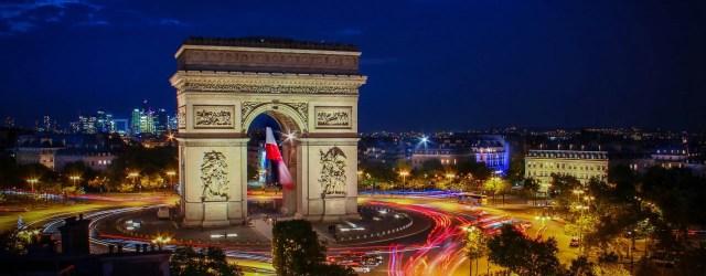 Arc de triomphe de Paris avec le drapeau français qui flotte, de nuit