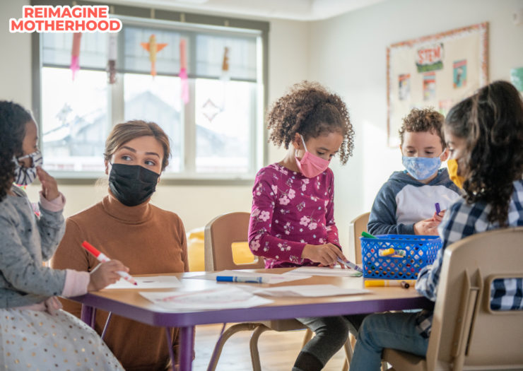 [PHOTO: Teacher at table with four kids]