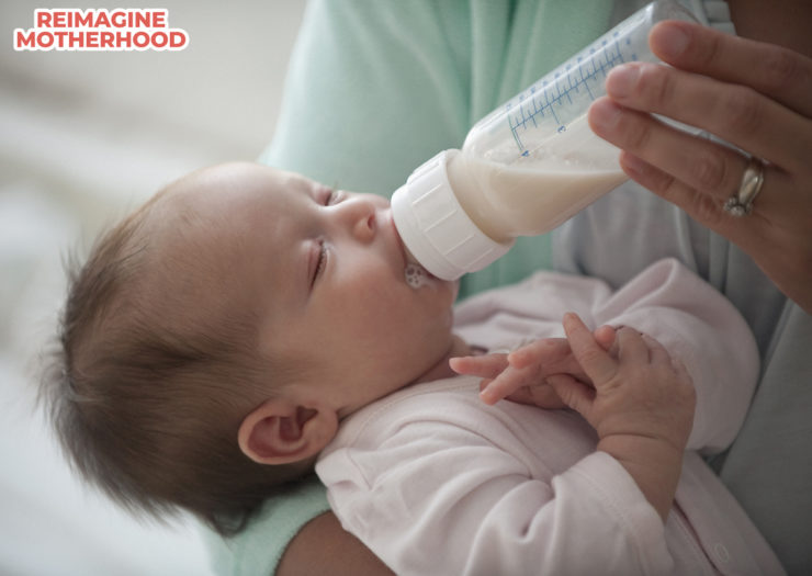 [PHOTO: Baby with eyes closed being fed a bottle of milk]