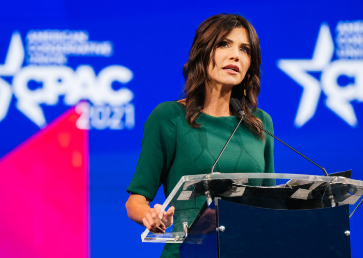 Photo of South Dakota governor Kristi Noem speaking behind a podium at a CPAC conference