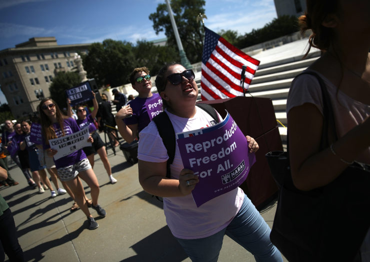 Photo of abortion rights rally where a demonstrator holds a sign that reads reproductive freedom for all