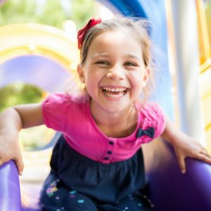 Little Girl Playing At Playground Outdoors In Summer