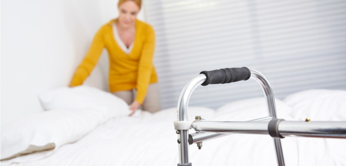 Woman fixing elderly persons bedding with a walker shown