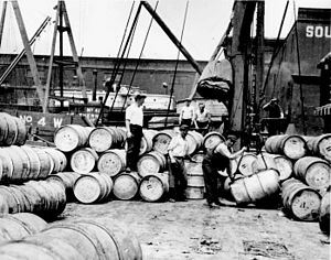 Stevedores on a NY dock loading barrels of corn syrup onto a barge on the Hudson River