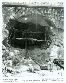 """Once land on the west side of Manhattan had been cleared of old tenement buildings, engineers excavated a construction shaft to provide vertical access to tunnel operations, including staircases on one side and electrical cables on the other for electricity and pipes carrying compressed air to keep the Hudson River from rushing into the tunnel. Within this shaft, workers known as """"Sandhogs"""" assembled the cutting shield, weighing over 400 pounds, to initiate the burrowing beneath the Hudson. Holes were first drilled at the face of the tunnel, and then the drill holes were loaded with explosives and detonated."""