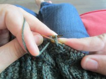 Hold the yarn down around the needle