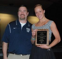 Soccer Coach Greg Rowe presents an award to Leah Benson