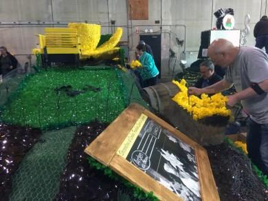 Deputy Mayor Kathy Hayden, Police Chief Brad Moericke and Mayor Bill Pugh start stuffing 10,000 daffodils into the float on Friday.