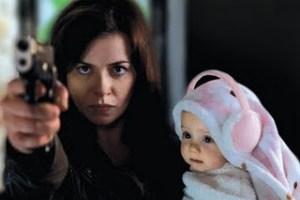 Gwen Cooper fires gun whilst holding her baby