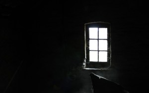 A small dusty window in a dark room.