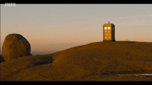 The TARDIS set on a slight rise in a barren landscape.