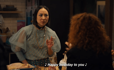 "An Asian woman smoking a join looks quizically at a red-haired woman. She is wearing a blue, puff-sleeved chiffon blouse. A caption with musical notes on either side reads ""Happy bithrday to you""."