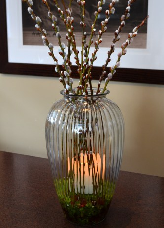 A candle is added to a vase filled with pussy willows.