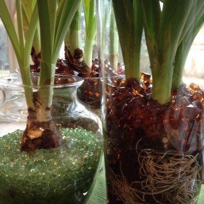 Brown and green beads with bulbs fill vases.