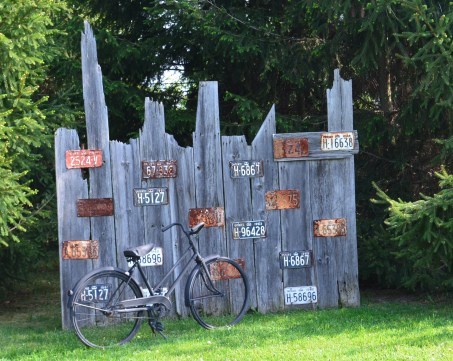 Old boards create a display for license plates in a garden.