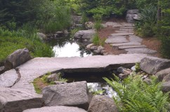 A slate foot bridge spans a small water feature in a woodland garden
