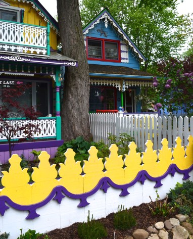 A fence is intricately carved and painted yellow, white and purple.