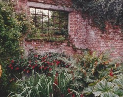 A window in an old brick wall which separates two gardens at Sissinghurst.