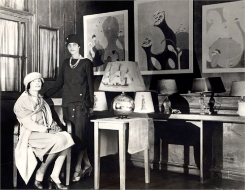 ca. 1926, Paris, France --- Peggy Guggenheim (standing), well-known American society girl who recently joined the ranks of young American business women in Paris, opened a lamp shop with famous British artist Mina Loy (seated) in the heart of the French capital. --- Image by © Underwood & Underwood/Corbis