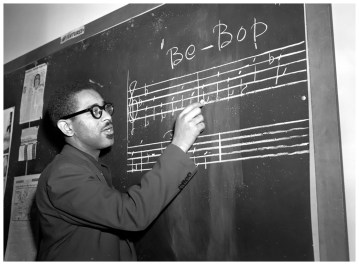 """Trumpeter Dizzy Gillespie writes a phrase of """"Be-Bop"""" music on the blackboard in New York, May 1, 1947. (AP Photo)"""