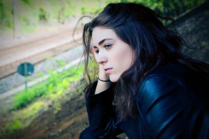 womanlooking pensively over railroad tracks, alcohol cravings