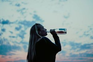 woman drinking from bottle at sunset, signs of alcoholism
